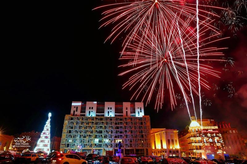 Fireworks go off near a giant Christmas tree, set in front of Martyrs'...